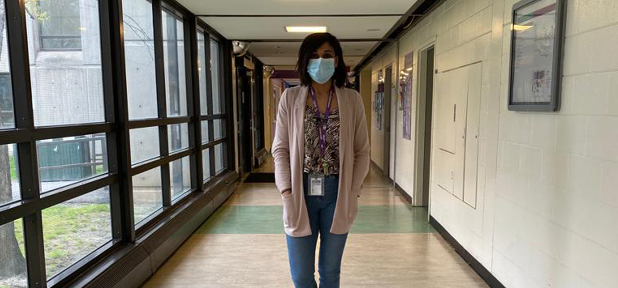 Aman wearing a mask and standing in a hallway at CAMH