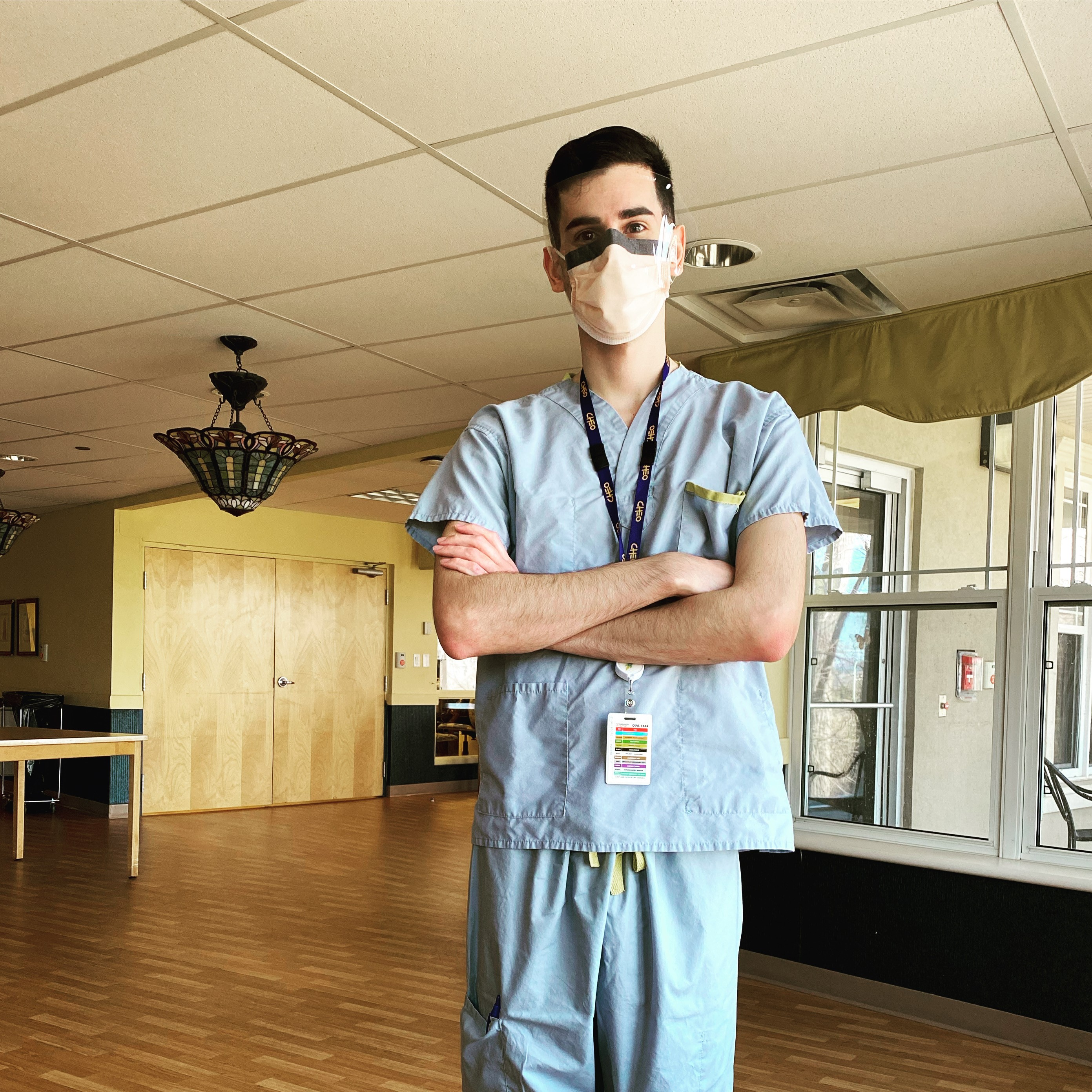 Brad Murphy in scrubs and a mask with his arms crossewd