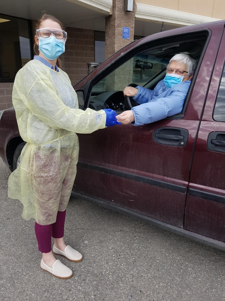 Dani Thomas wearing protective equipment and pricking a patient's finger while the patient sits in her vehicle