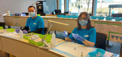 Ken Manson and Nancy Grindrod wearing PPE and working at the vaccine clinic