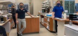Peter and Paul standing in their pharmacy wearing masks