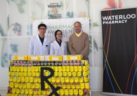 Students and director Dave Edwards stand behind dispensary counter made of cans.