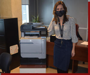 Kaitlin wearing a mask next to a printer