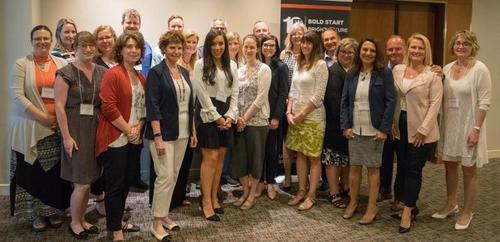 Group of men and women standing and smiling at smoking cessation initiative meeting