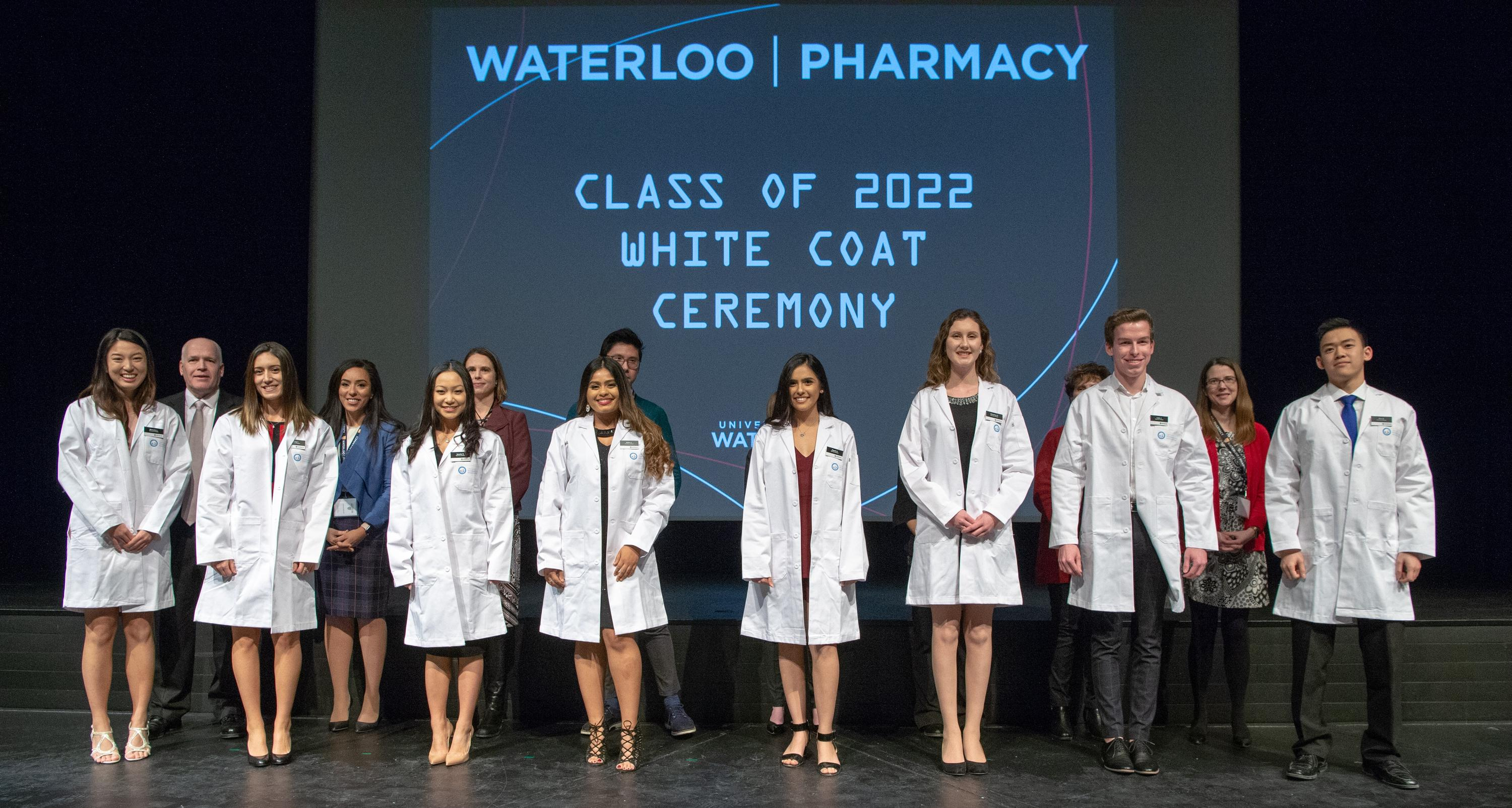 8 students recieving robes on stage at white coat ceremony