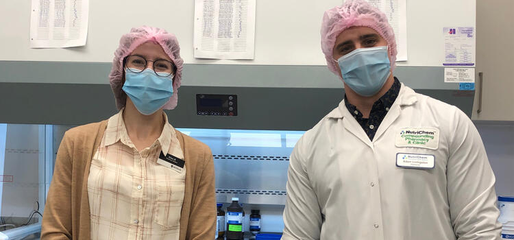 Elisa and Adam in the compounding lab wearing masks