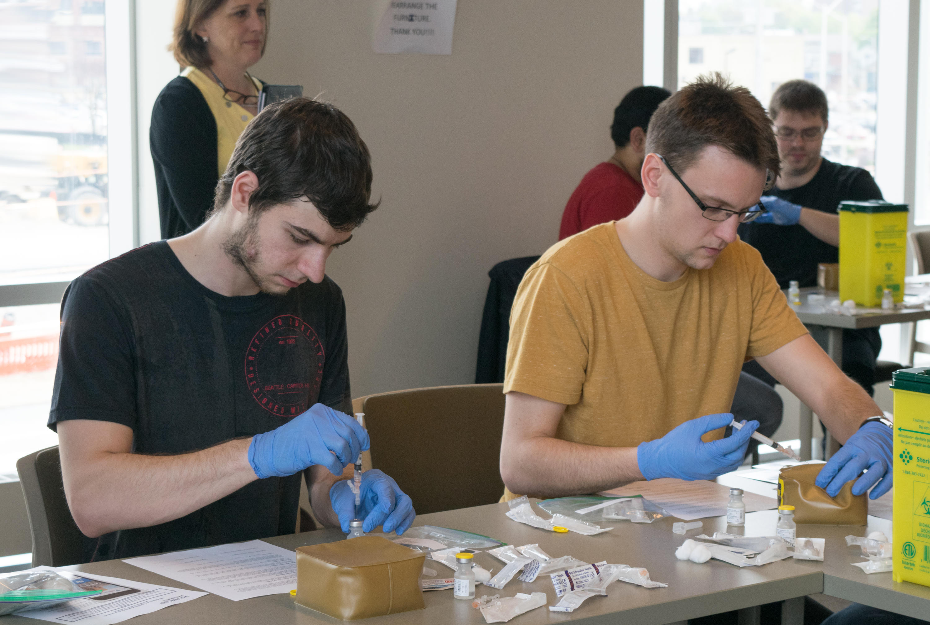 Two students learning how to prep needles for vaccinations