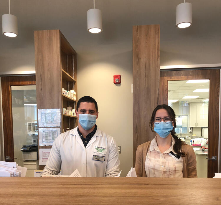 Adam and Elisa behind the dispensary wearing masks at the NutirChem Pharmacy