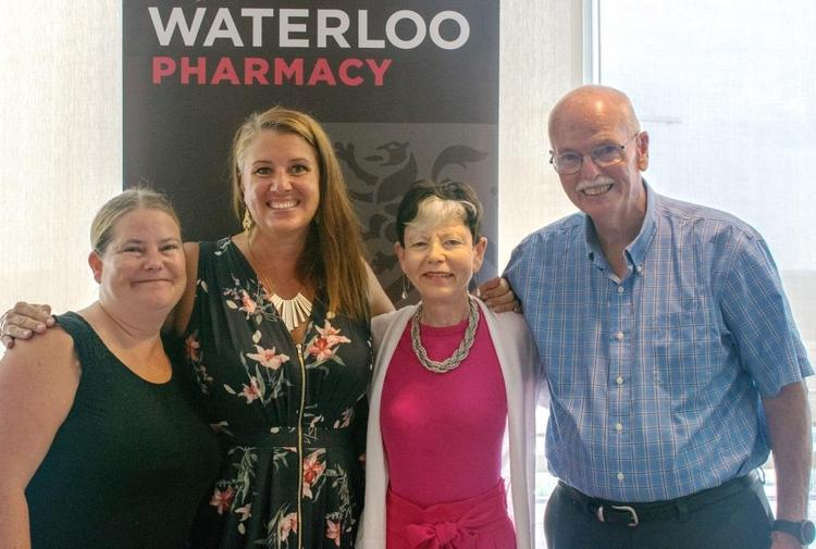 Elaine and her family in front of a Waterloo Pharmacy sign