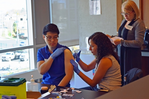 PharmD Bridging Student injecting another student during injection training workshop.