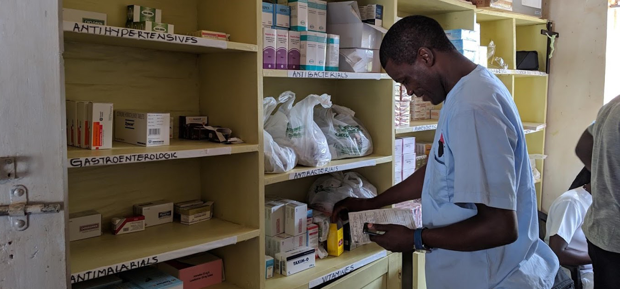 A member of CACHA checking stock on the shelves of the clinic