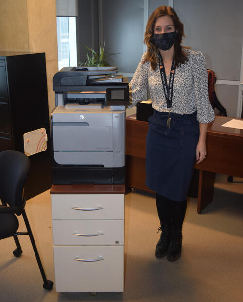 Kaitlin Bykoski wearing a mask next to her printer