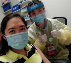 Michelle Liang and a patient, both wearing masks, after giving a flu injection