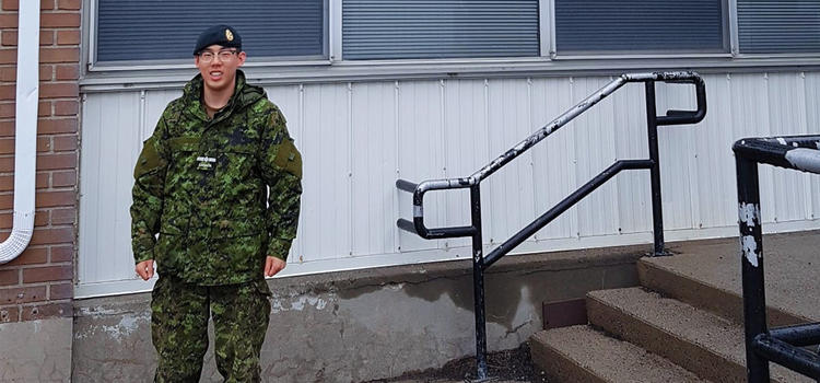 Sean standing outside the medical clinic in military attire