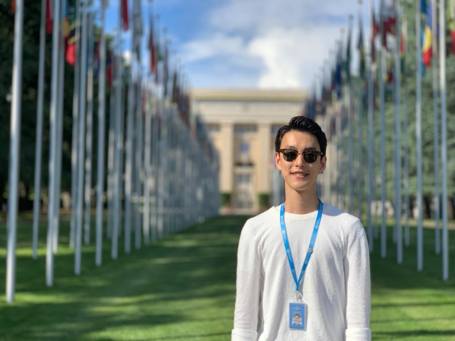 John standing outside the United Nations building on a field of grass