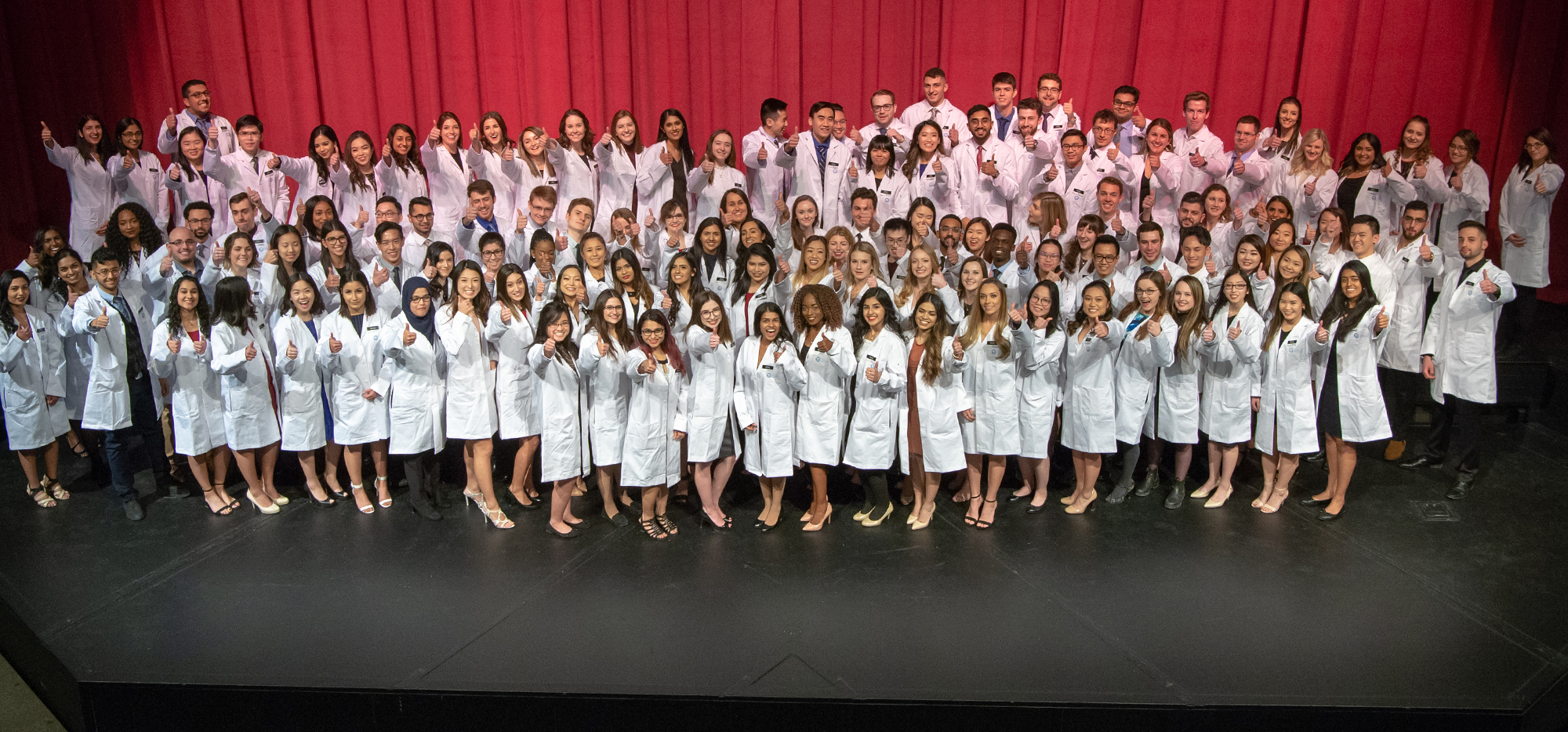 Class of 2022 in their white coats giving thumbs up