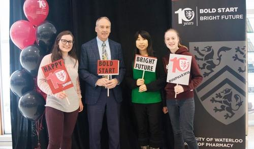 Dave Edward and three students holding bold start, bright future signs.
