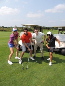 Four golfers with clubs ready to play