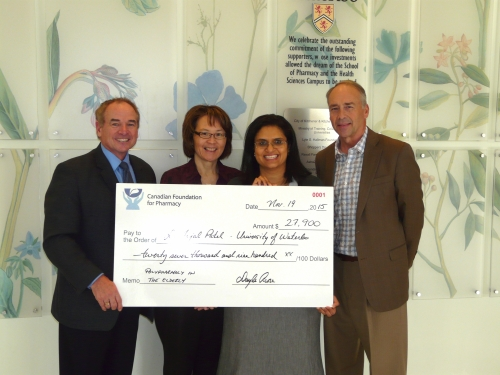 Professor Patel receiving research grant from Canadian Foundation of Pharmacy individuals standing in lobby with large cheque