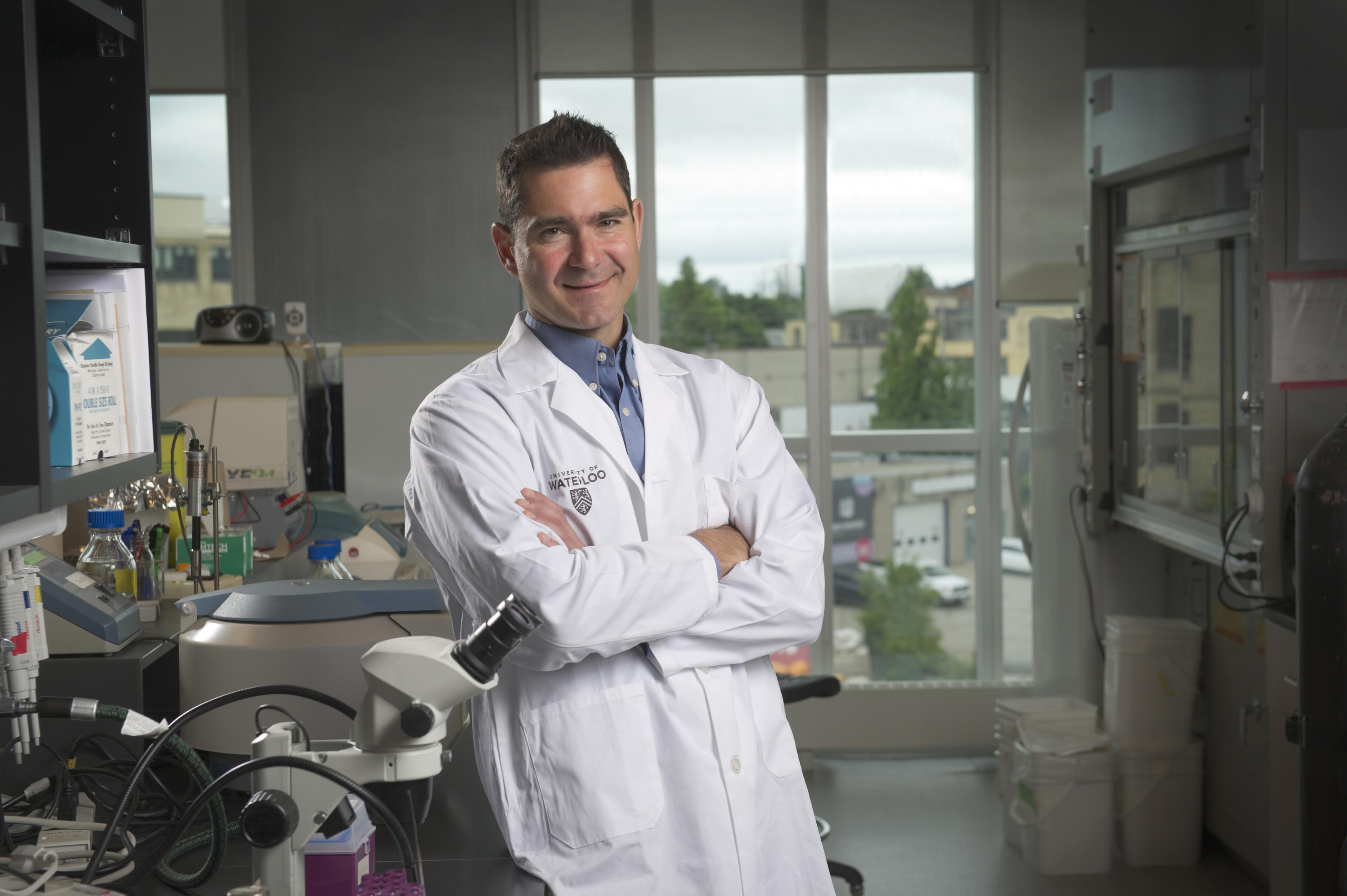 Roderick Slavcev in a lab coat standing in lab