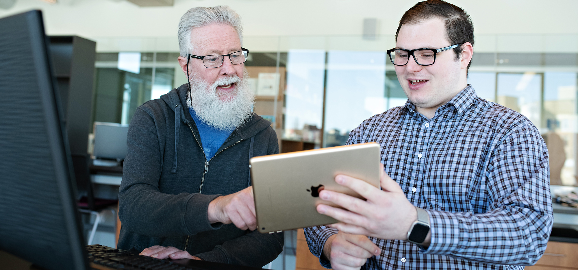 Colin holding a tablet and gesturing to it while an older adult with glasses watches