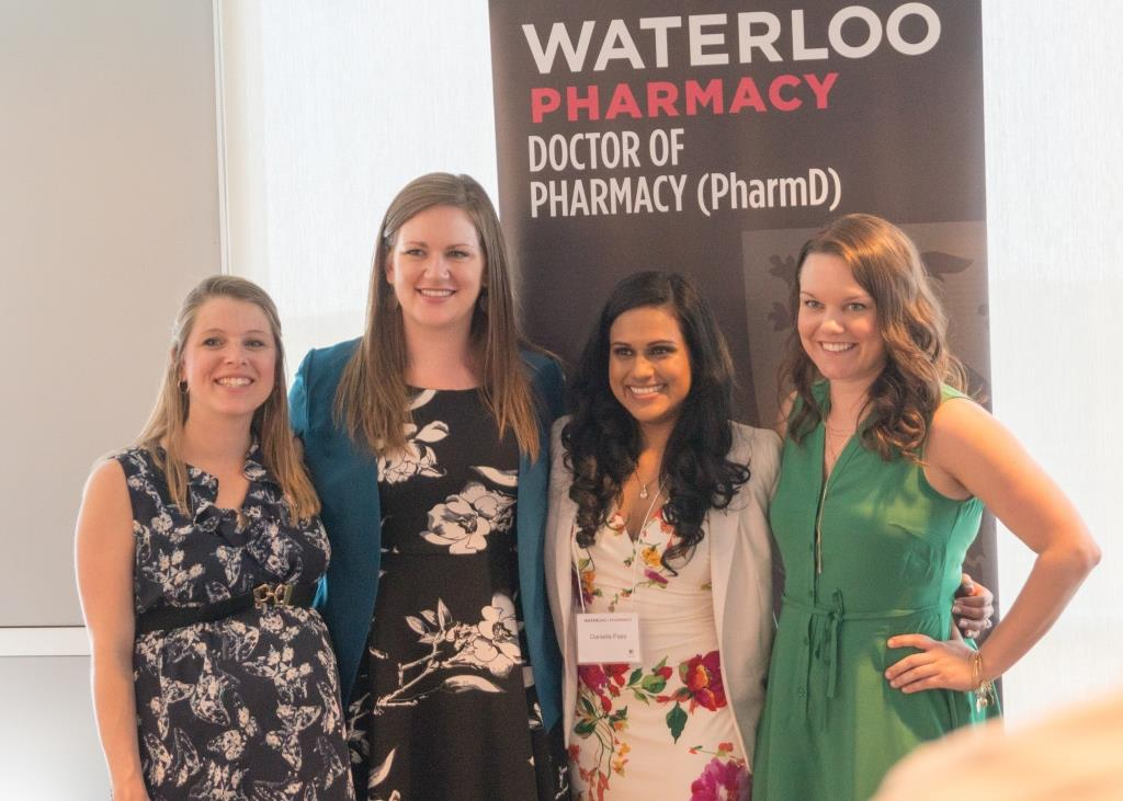 Four PharmD bridging program graduates in front of a sign that reads Waterloo Pharmacy Doctor of Pharmacy (PharmD)