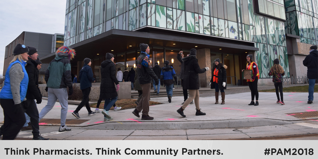 Think Pharmacists. Think Community Partners. #Pam2018. People walking outside the School of Pharmacy.