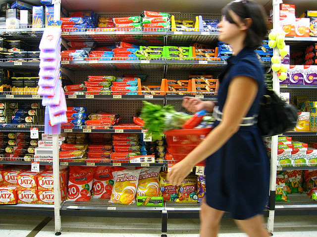 Woman walks through grocery store aisle.