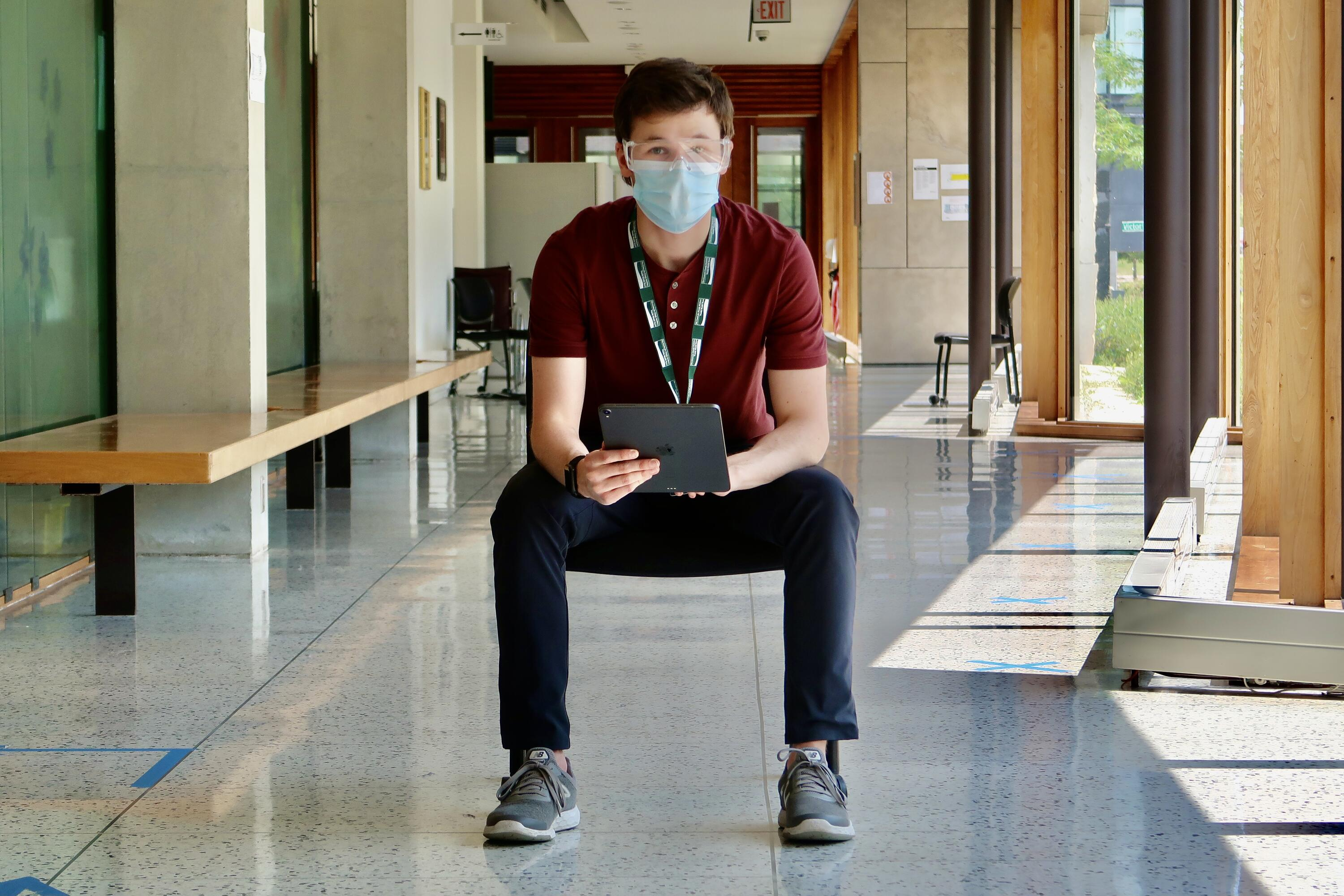 Ryan wearing PPE in a hallway with a tablet