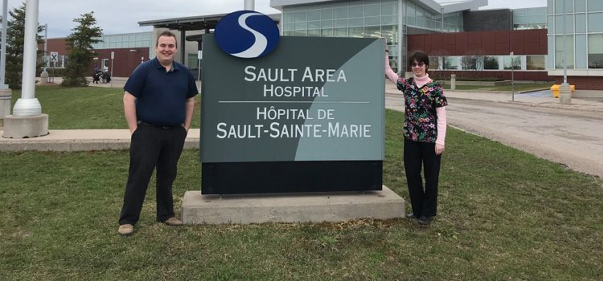 Nick and Krista standing next to a sign that says Sault Area Hospital