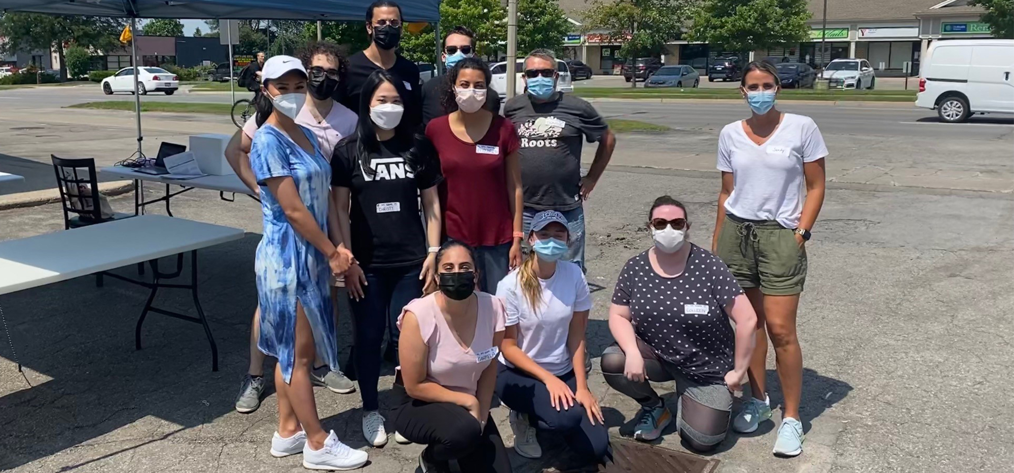The team that ran the clinic smiling and wearing masks in a parking lot