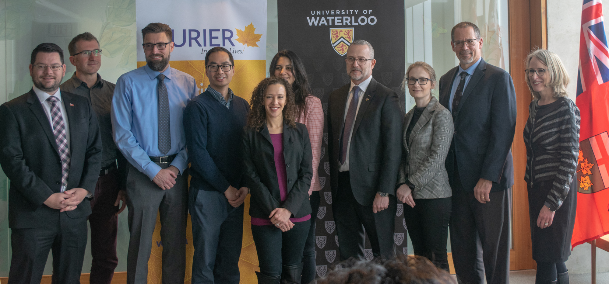 Representatives from the University of Waterloo, Laurier University and the Ontario Government standing and smiling