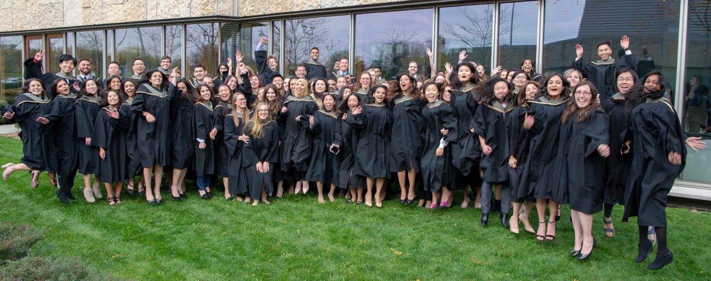 Class of Rx2018 in graduation gowns jumping
