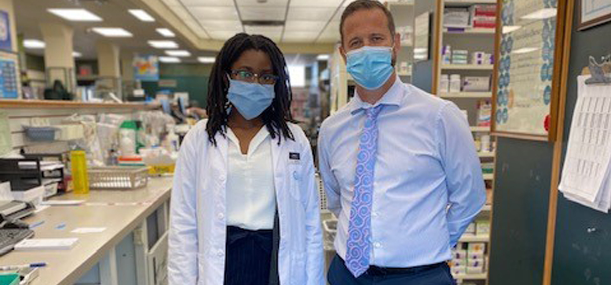 Carolyn Lawrence and Steven Bond wearing masks in the pharmacy