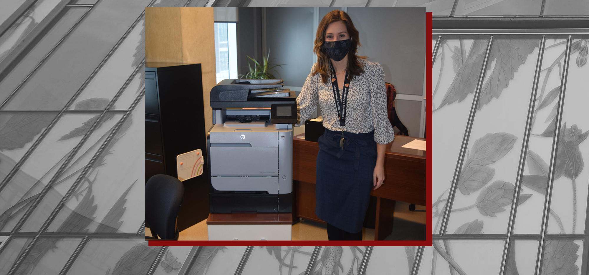 Kaitlin wearing a mask and standing next to a printer