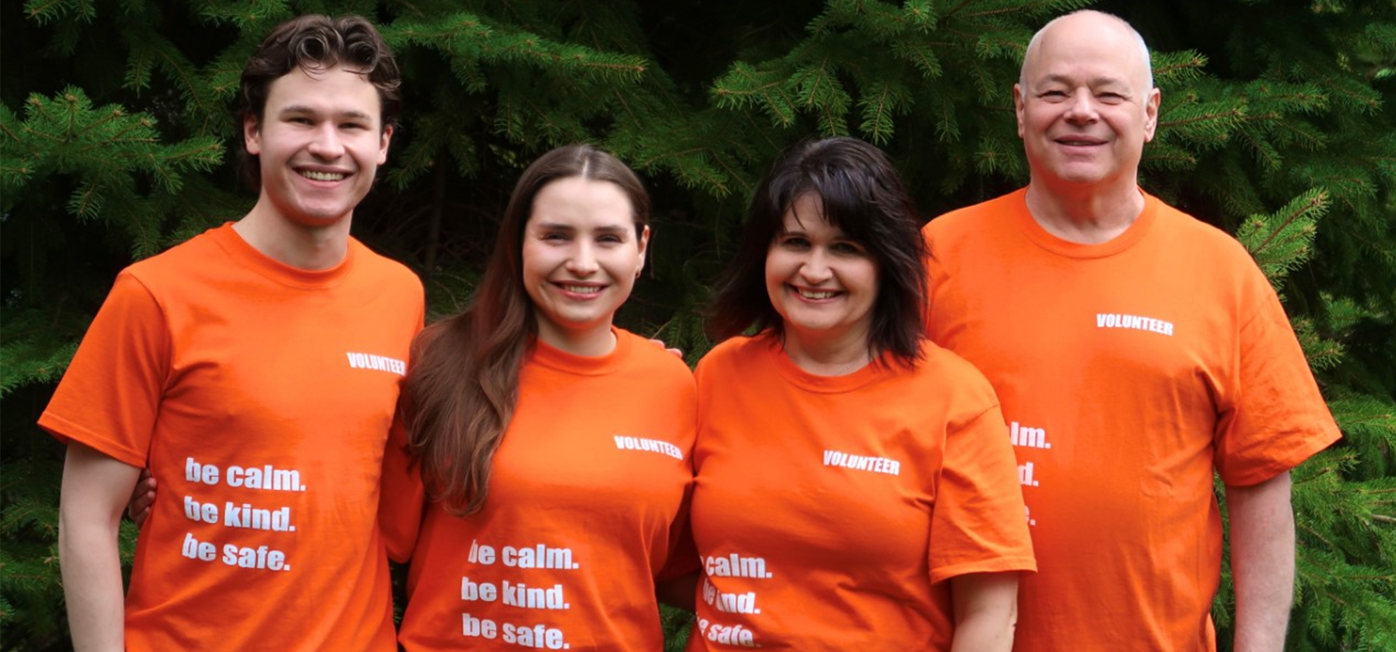 The Tennant family (four people) wearing orange shirts in front of some trees