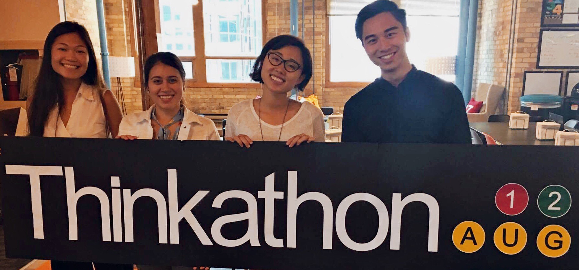 Two Think Research employees with Rui Su and Kelvin Yam holding a Thinkathon sign