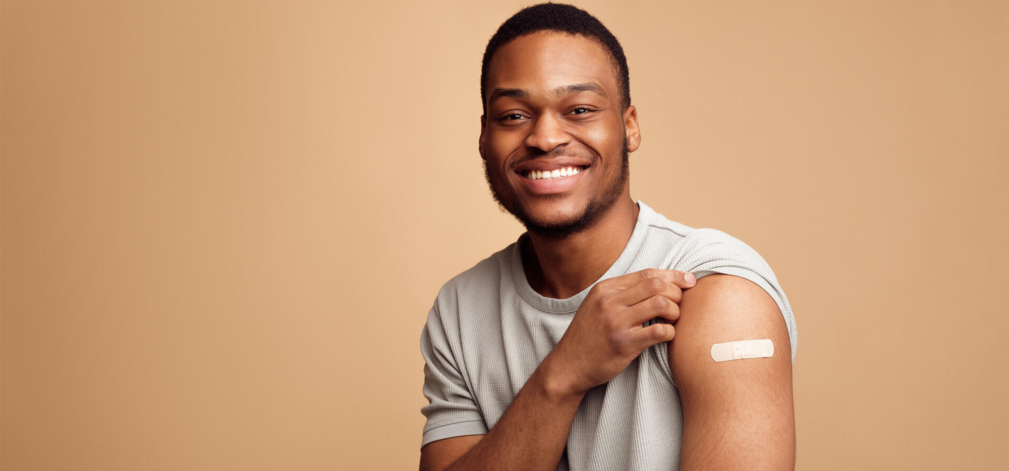 a man rolling up his sleeve and showing a vaccination band-aid
