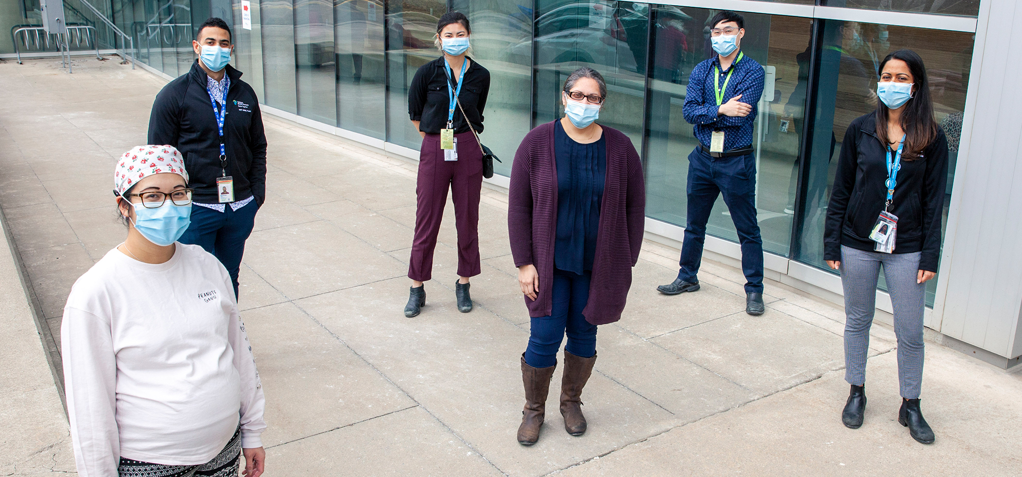 A team of healthcare providers wearing masks and socially distanced outside a hospital