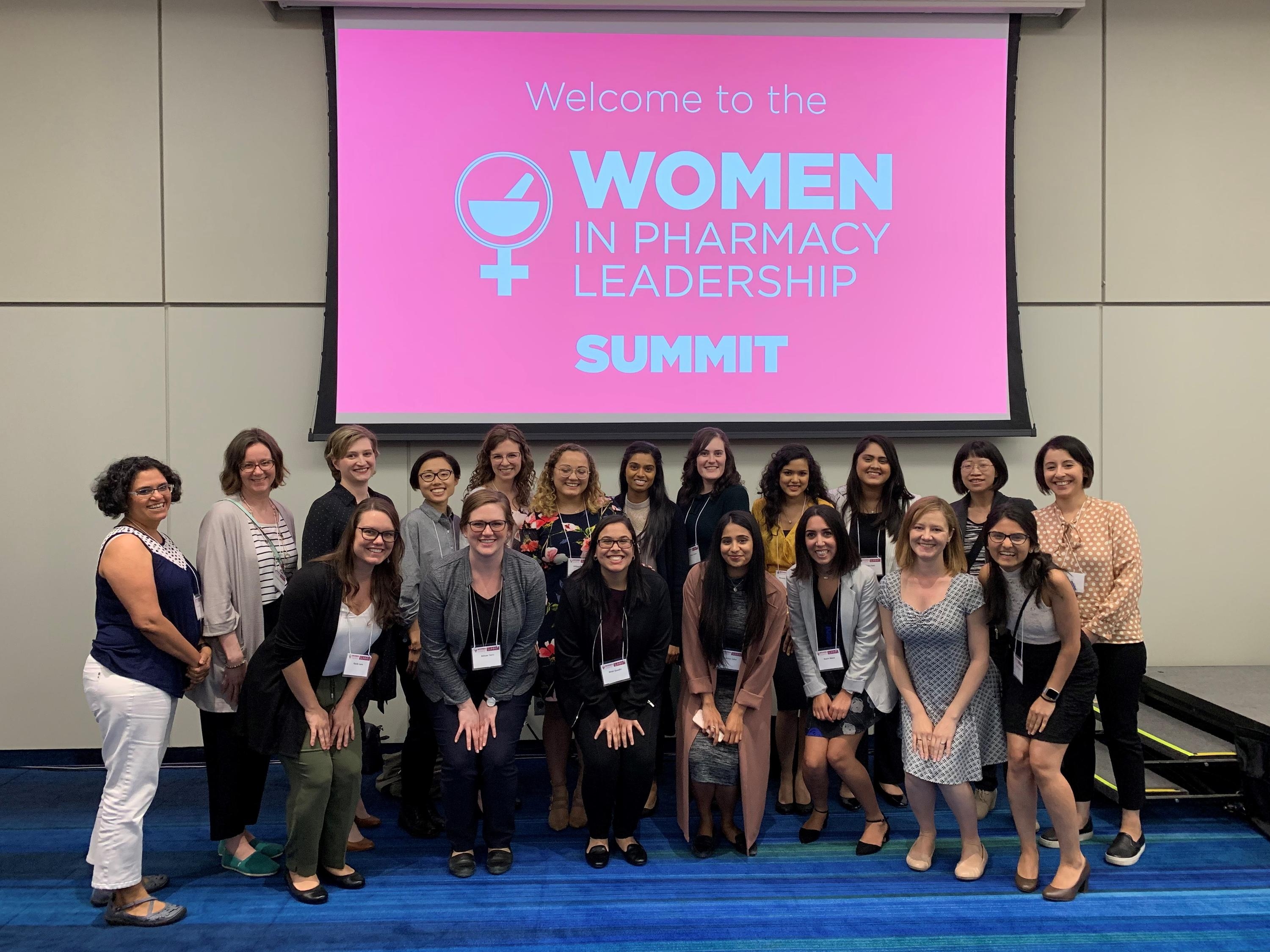 Waterloo Pharmacy faculty, alumni and students stand in front of a banner that says Women in Pharmacy Leadership Summit.