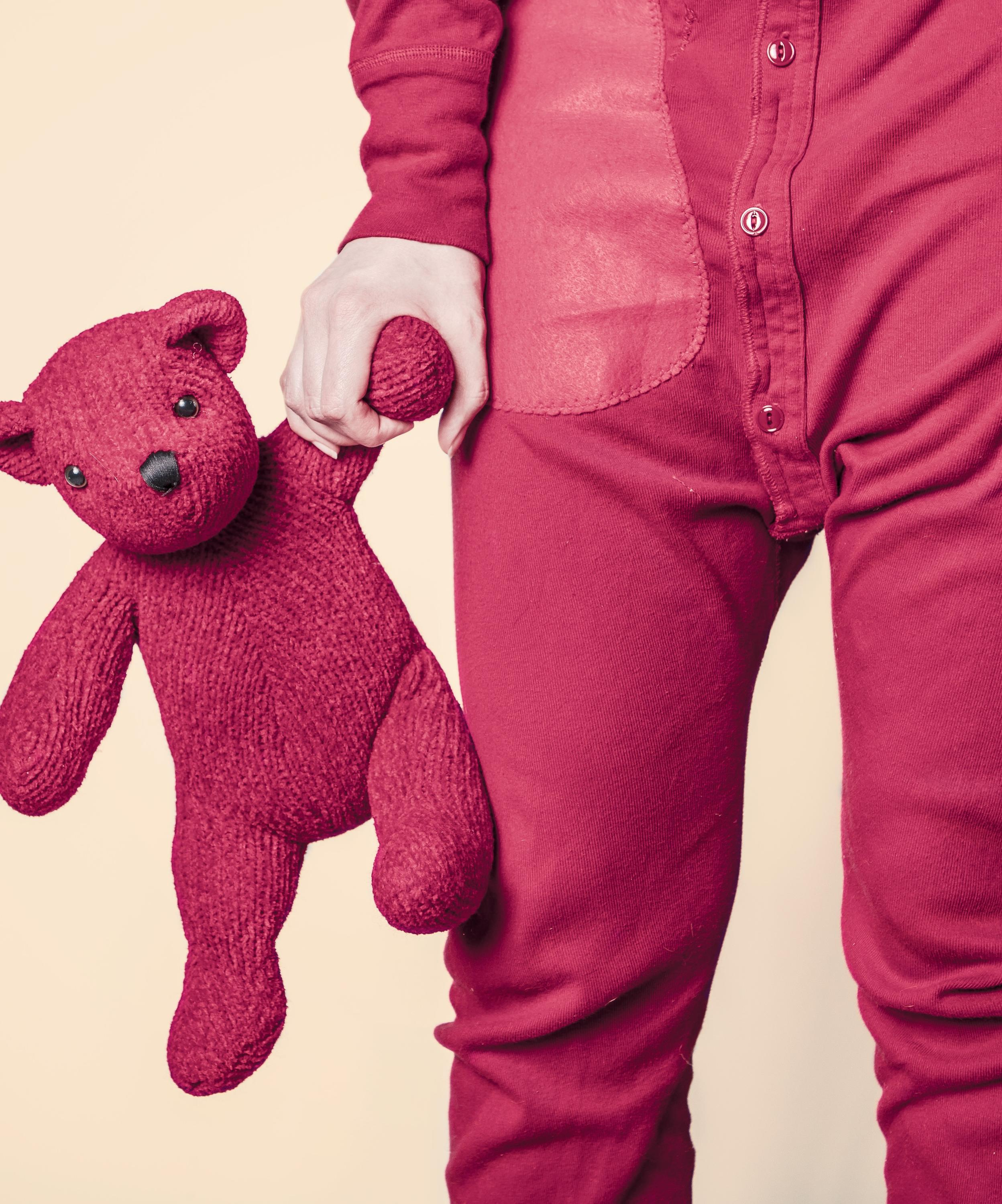Person in red pajamas holding a teddy bear