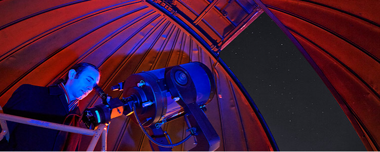Astronomer using the telescope in the Gustav Bakos Observatory, taken in red light.