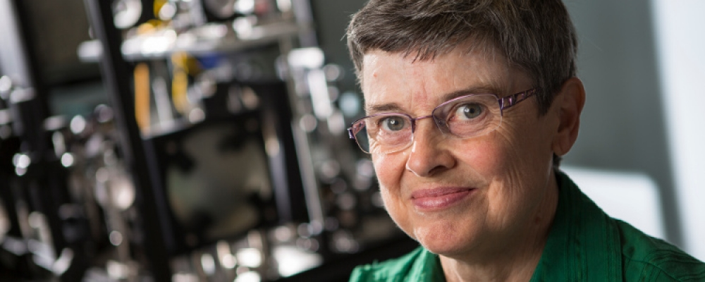 Professor Melanie Campbell stands before optical imaging equipment