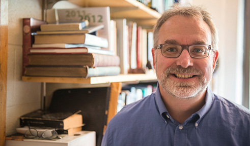 Dr. David Drabold in an office with a backdrop of books on a shelf