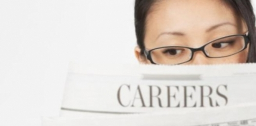 "A woman reading the ""Careers"" section of a newspaper."