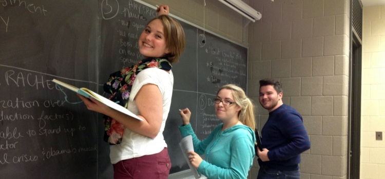 Students writing on chalkboard