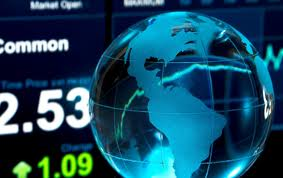 Globe infront of screen with global stock exchange data.