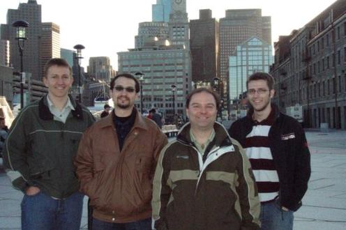 ASPE Topical Meeting (Boston), April 2010. Four men standing in front of Boston skyline.
