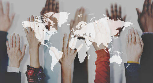 Map of the world overlaid onto an image of many hands raised
