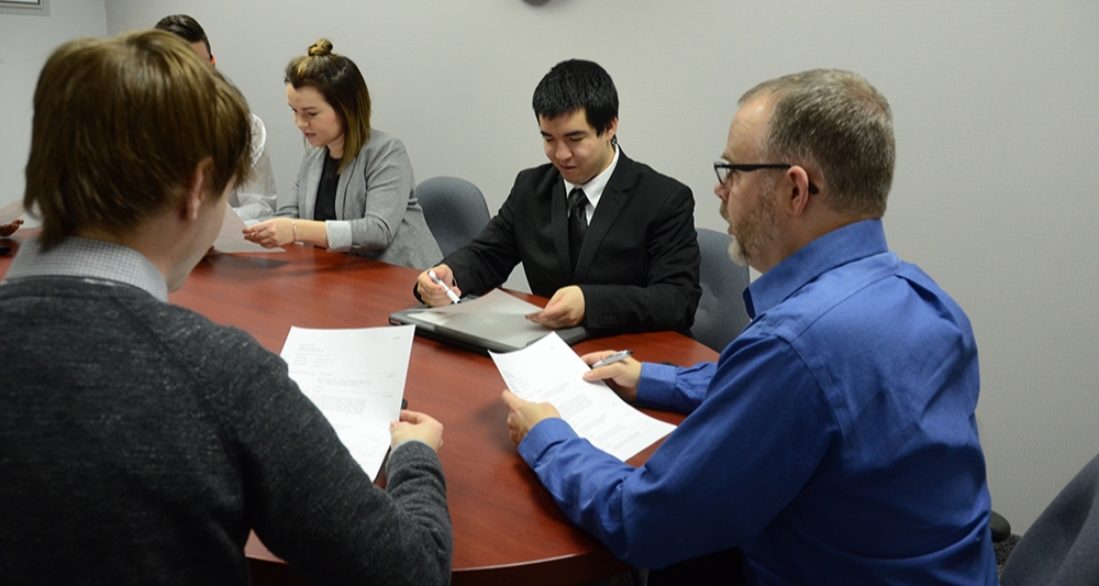 Students in a meeting with supervisor